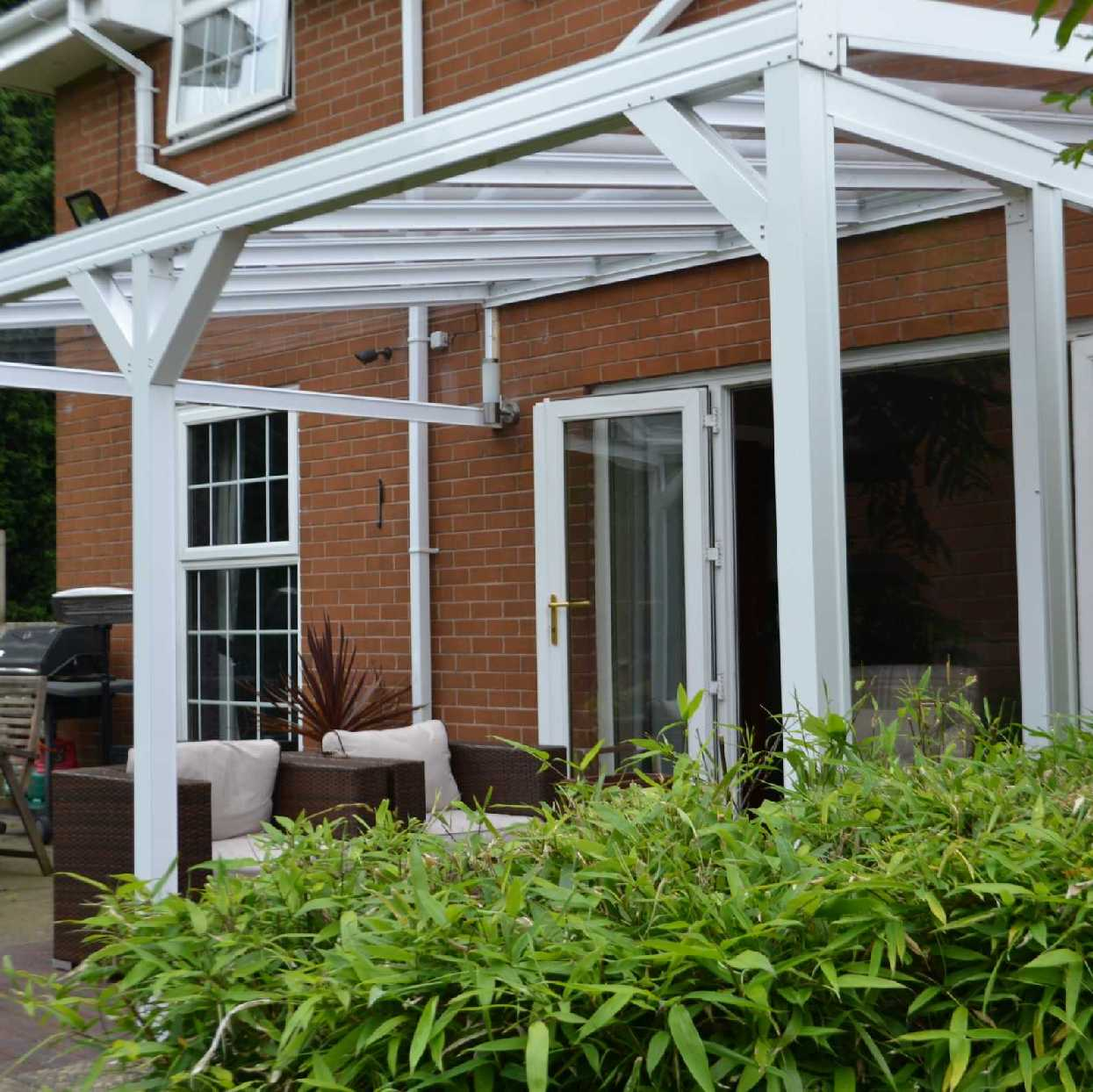 Omega Smart White Lean-To Canopy with 6mm Glass Clear Plate Polycarbonate Glazing - 7.7m (W) x 2.5m (P), (4) Supporting Posts from Omega Build